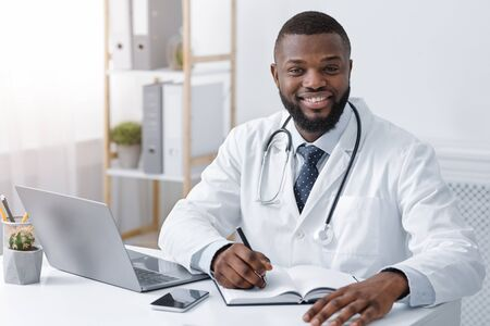 Happy black physician taking notes while working online from clinic, consulting patients online during quarantine