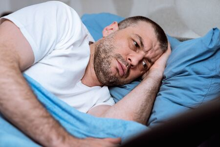 Anxiety And Sleeplessness. Middle-Aged Man Having Insomnia Lying In Bed At Home During Coronavirus Self-Isolation