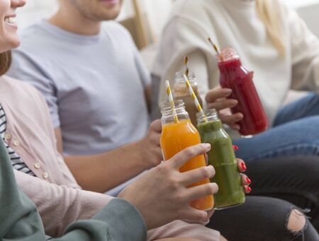 Modern friends drinking colored healthy detox smoothie at home, healthy party