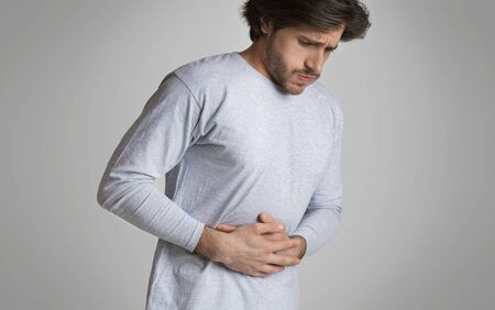 Young man hands on stomach, having bad aches pain. Food poisoning, influenza, cramps