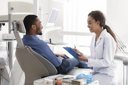 Smiling black female dentist filling medical chart, talking to patient in dentist chair, clinic interior