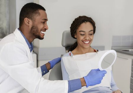 Friendly black dentist giving mirror to his happy female patient Stockfoto
