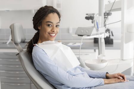 Young black lady sitting in dentist chair and smiling at camera, copy space Stockfoto