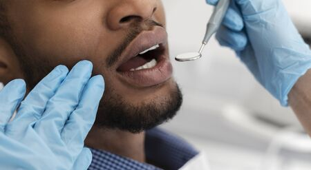 Cropped of dentist hands in gloves checking black man mouth with tools