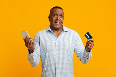 Online transaction problem. Confused middle african american man using mobile banking and credit card