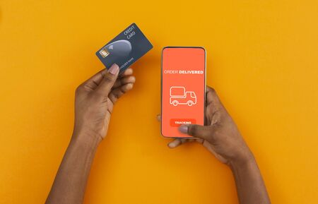 Stay at home, pay with credit card. African american man ordered with online app on cell phone, yellow background
