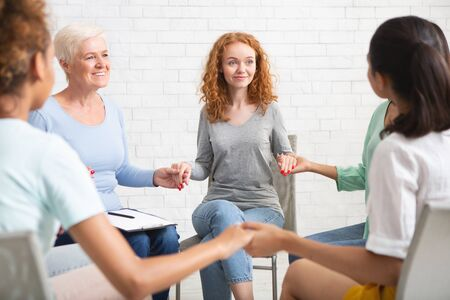 Female Support. Multicultural Women Holding Hands Sitting In Circle During Group Therapy Session Indoors. Selective Focus