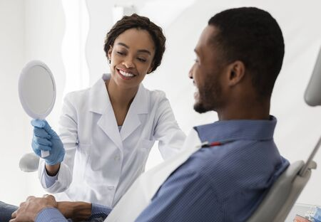 Pretty black female dentist holding mirror for male patient, checking final result