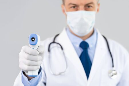 Closeup portrait of doctor wearing protective surgical mask ready to use infrared forehead thermometer gun