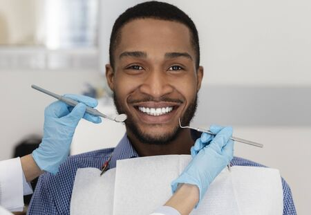 African guy in dentist chair smiling at camera, close up