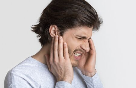 Man with earache is holding sore spot, profile on light background