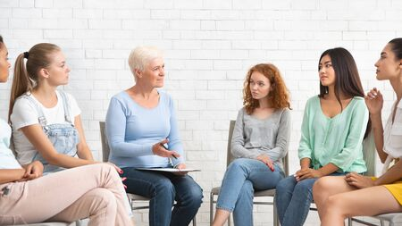 Professional Psychotherapist Talking With Women During Group Therapy Session Sitting Indoors. Panorama, Selective Focus