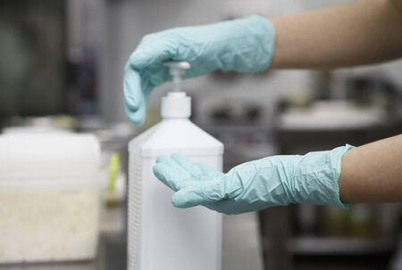 Woman disinfecting hands with alcohol gel sanitizer in kitchen before cooking. Quarantine, outbreak coronavirus