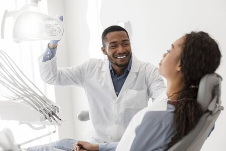 Cheerful black dentist turning on equipment before check up and greeting female patient Stock Photo