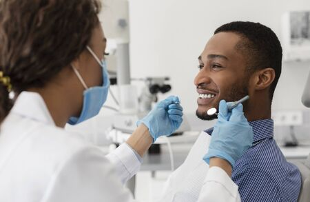 Young african guy smiling to his female dentist while having treatment at modern clinic