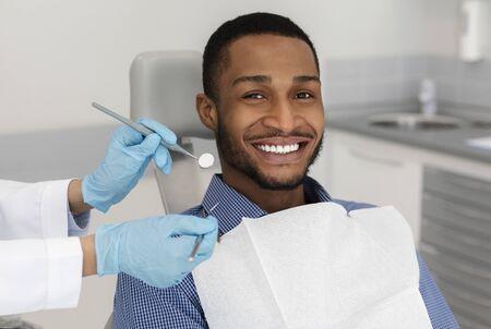 Recadrée d'outils de dentiste dans les mains d'un médecin et d'un homme africain joyeux dans une chaise de dentiste