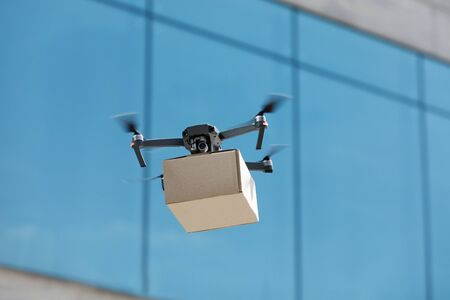 Fast drone flying through the air with a delivery box package clamped on to deliver to customer