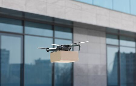New generation of delivery, fast and safe. Modern drone delivering small parcel, panorama, copy space