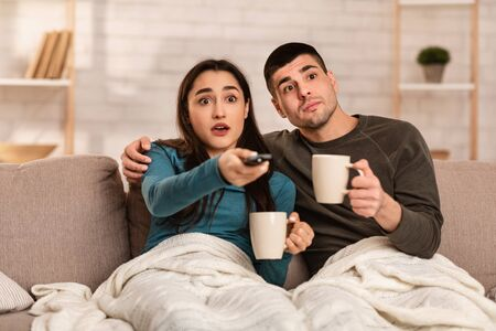 Shocking News. Amazed couple drinking hot tea and watching scary horror movie, wrapped in warm blanket, copy space