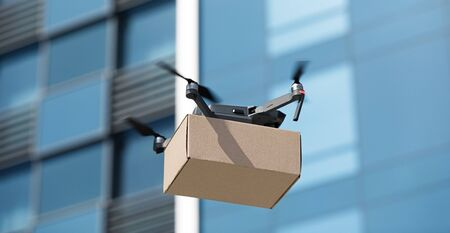 Air logistic of the future. Electric drone delivering small box through the city, panorama Stockfoto