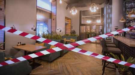 Quarantine Zone Warning Tape, Do Not Cross Concept. Red and white hazard safety stripes across empty closed cozy restaurant