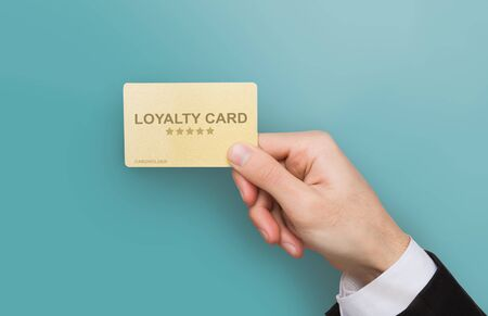 Consumer friendly marketing concept. Closeup of businessman hand holding loyalty card on blue background. Collage