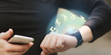 Exercising Outdoors. Unrecognizable Man Checking Activity Tracker With Icons On Wrist Watch And Holding Smart Phone