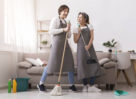 Millennial couple having fun while cleaning house, singing and fooling together at home, tidying apartment with pleasure, free space