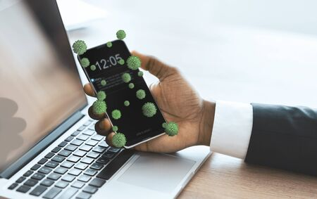 Cropped of african american businessman holding smartphone with virus cells on it and working on laptop in office
