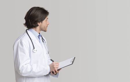 Confident doctor in white coat writing notes on clipboard and looking at copy space on light background