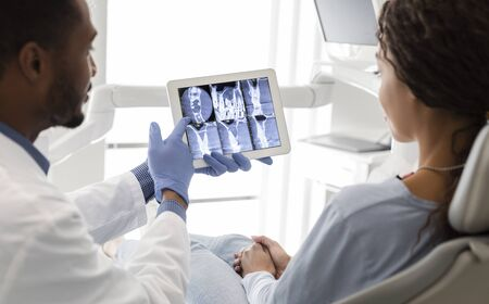 Black dentist and female patient looking at xray picture on digital screen at clinic