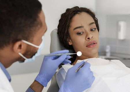 Scared black woman looking with fear at dental tools in doctor hands, dentophobia concept Stockfoto