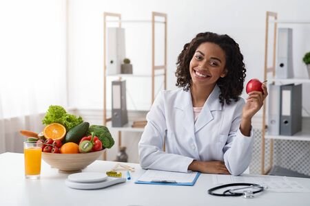 Diet while lockdown. Pretty black lady dietologist holding apple in her hand and smiling, recommending fresh fruits, posing at clinic, copy space
