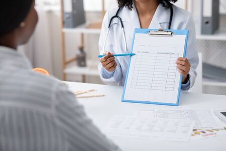 Black dietician showing female patient treatment plan, cropped, clinic interior