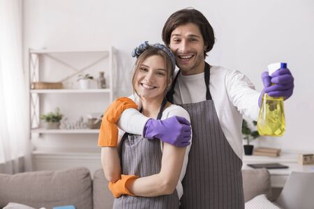 Romantic Couple Tidying Flat Together, Hugging And Posing To Camera, Holding Sprayer And Wearing Rubber Gloves, Copy Space