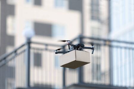 New smart drone with parcel, package delivery robot. Contactless air remote transportation, blurred background Stockfoto