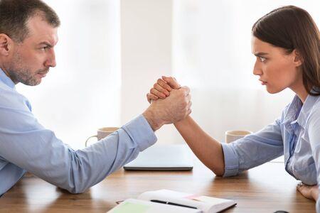 Businessmen Vs Businesswomen Competition. Businessman And Businesswoman Arm Wrestling Arguing Whos Stronger Sitting At Work Desk In Modern Office. Stock Photo