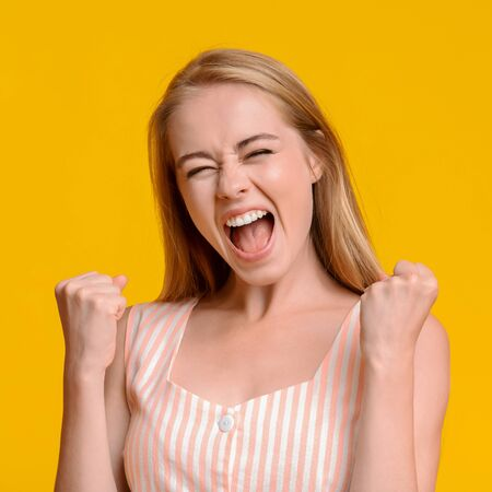 Crazy Sales. Pretty Young Girl Emotionally Shouting With Raised Fists, Celebrating Success Over Yellow Background, Copy Space