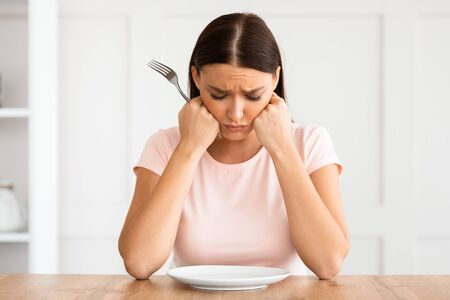 Dieting Concept. Unhappy Woman Looking At Empty Plate Losing Weight Sitting At Table At Home.