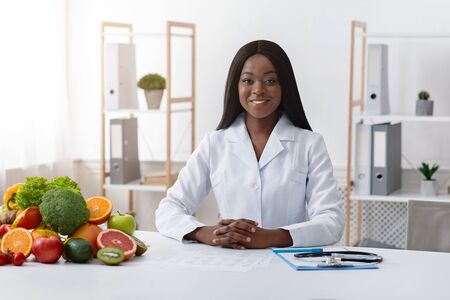 Beautiful young black woman nutritionist posing at her workplace, copy space