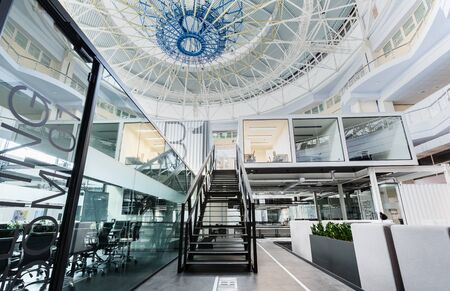 Modern open space office with high ceilings and dome, transparent walls