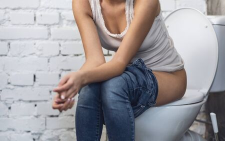 Woman Sitting On Toilet Having Diarrhea Problem Digestive Disorder In Bathroom At Home. Defecation Concept. Cropped Stock Photo