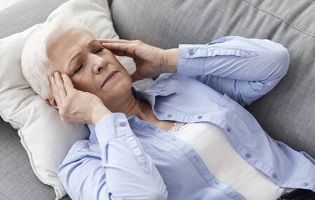 Migraine At Senior Age. Elderly Woman Having Strong Headache, Lying On Couch Massaging Temples, Closeup