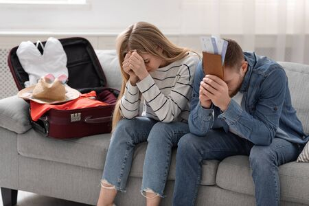 Travel restriction. Desperate couple sitting near packed suitcase at home