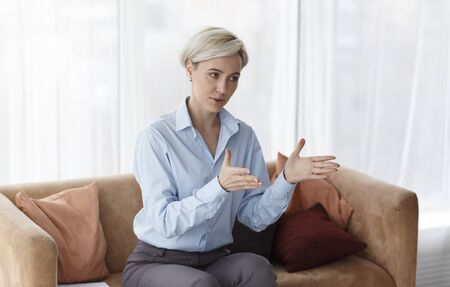Psychotherapy Concept. Professional Psychologist Giving Advice During Therapy Session Sitting On Sofa In Office. Stock Photo