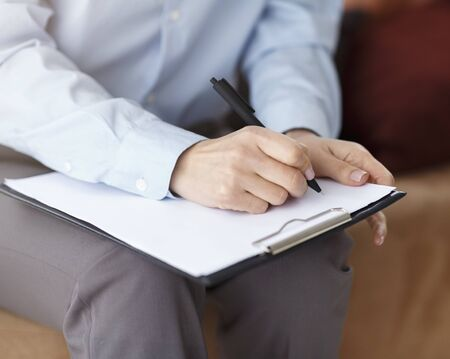 Unrecognizable Professional Psychologist Taking Notes Holding Folder Sitting On Couch In Office. Cropped, Closeup Stock Photo