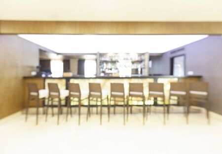 Blurred photo of bar in hotel with high chairs and bright lighting