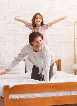 Excited little girl riding her cheerful dad, bedroom interior