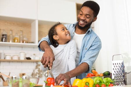 Cute african daughter looking at cheerful daddy with love, cooking together helthy salad in kitchen, empty space Stockfoto