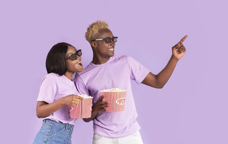 Home cinema concept. African American guy and girl with 3D glasses and popcorn picking movie to watch on lilac background